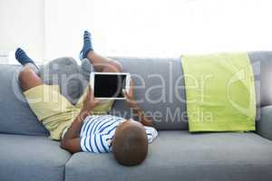 Boy lying on sofa while using digital tablet at home