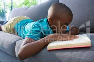 Boy reading novel while lying on sofa at home