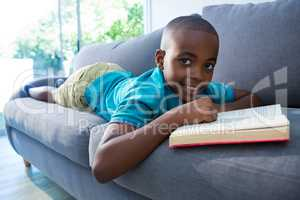 Boy lying on sofa with novel at home