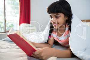 Smiling girl reading novel on bed at home