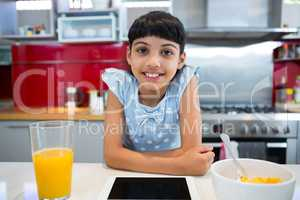 Portrait of smiling girl sitting with tablet and breakfast in kitchen
