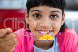 Close-up of portrait of girl holding cereal in spoon