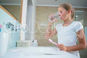 Girl drinking water while holding toothbrush in bathroom