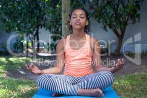 Full length of girl meditating in yard