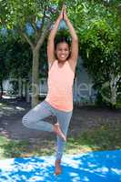 Portrait of smiling girl doing tree pose yoga