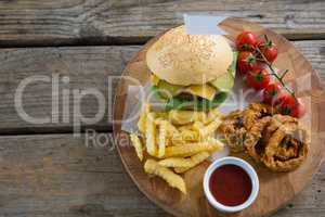 Overhead view of burger and fries with onion rings by sauce