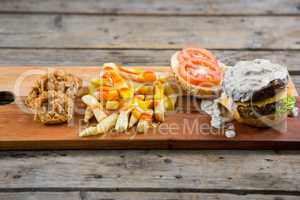 French fries with sauce by onion rings and burger on cutting board