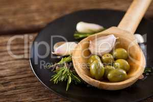 Green olives, rosemary and wooden ladle on table