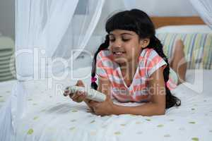 Girl pressing remote control while lying on bed