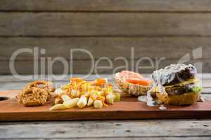 French fries with sauce by burger and onion rings on cutting board
