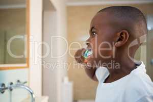 Side view of boy brushing teeth