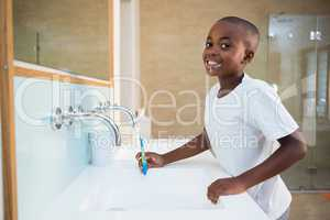 Portrait of smiling boy standing by sink with toothbrush
