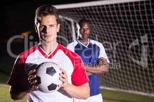 Portrait of confident soccer player holding ball with rival athlete