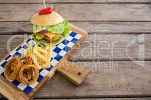 High angle view of onion rings and french fries with burger