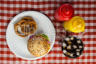 Hamburger, french fries, onion ring and cold drink on napkin