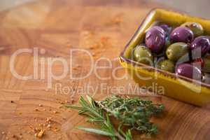 Marinated olives with herbs and chili in container on table