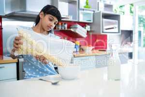 Girl pouring breakfast cereal in bowl