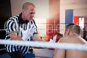 Referee gesturing to male boxer in ring