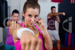 Portrait of young female practicing boxing against flags