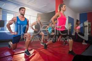 Young athletes practicing lunge exercise on mats