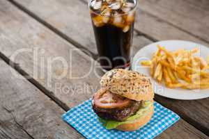 Hamburger on napkin with french fries in table by drink