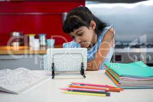 Girl using digital tablet amidst colored pencils and books