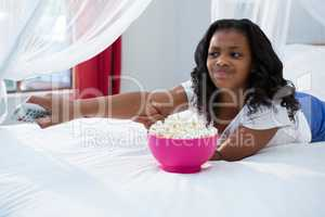Girl changing channel while watching television