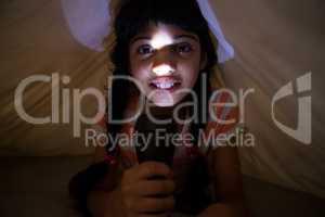 Close-up portrait of girl holding illuminated flashlight under blanket