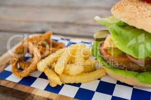 Close up of onion rings and french fries with burger