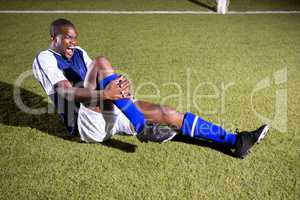 Young male soccer player shouting in agony with knee pain