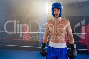 Portrait of confident shirtless boxer wearing protective sportsgear