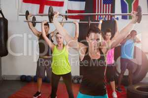 Young athletes lifting barbells against flags