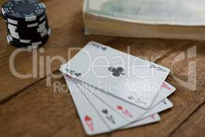 Close-up of four aces by chips and money