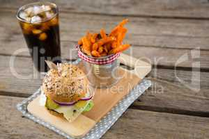 French fries by burger on cutting board with drink