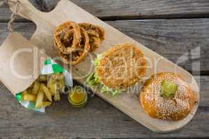 Overhead view of burger with onion rings and french fries