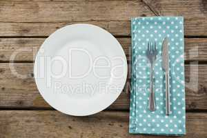 Overhead view of empty plate by napkin and eating utensils