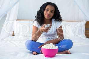 Girl holding remote control while watching television