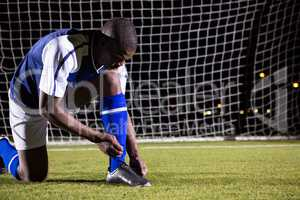 Male soccer player tying shoelace on field
