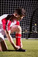 Young male soccer player tying shoelace against goal post