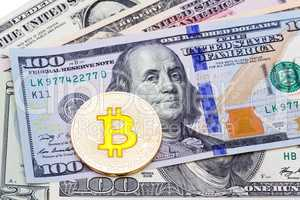 Closeup of golden yellow bitcoin on hundred dollars banknote, ma