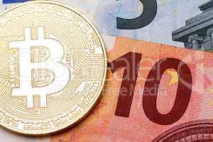 Ten euro banknote as a background for golden bitcoin.