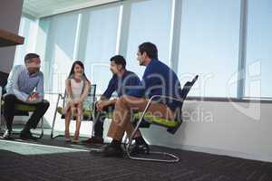 Business people communicating while sitting on chairs by window at office