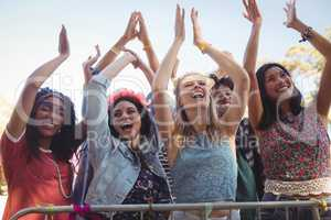Low angle view of cheerful female fans enjoying music festival