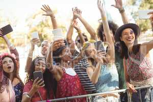 Smiling friends taking selfie through their mobile phones at music festival