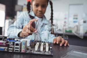 Elementary girl assembling circuit board at electronics lab