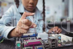 Mid section of elementary girl assembling circuit board