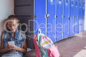 Elementary student listening music through headphones while using smartphone