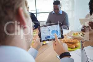 Businessman using digital tablet at breakfast table