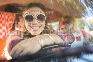 Smiling woman in camper van seen through windshield