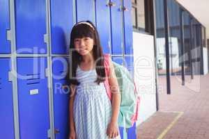 Portrait of elementary schoolgirl standing by lockers